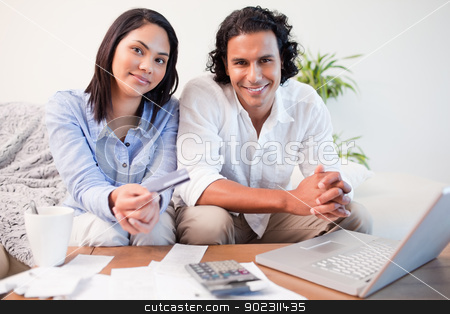 Couple doing online banking in the living room stock photo, Young couple doing online banking in the living room by Wavebreak Media