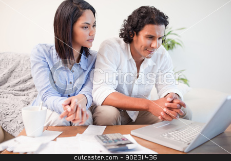 Couple sitting in the living room doing online banking stock photo, Young couple sitting in the living room doing online banking by Wavebreak Media