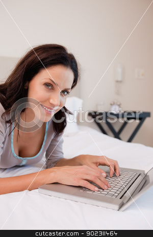 Smiling woman with notebook on the bed stock photo, Smiling young woman with notebook on the bed by Wavebreak Media