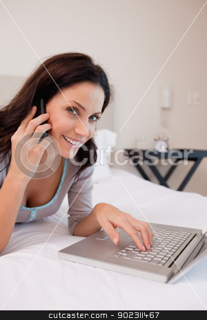 Side view of smiling woman with laptop and phone on the bed stock photo, Side view of smiling young woman with laptop and phone on the bed by Wavebreak Media