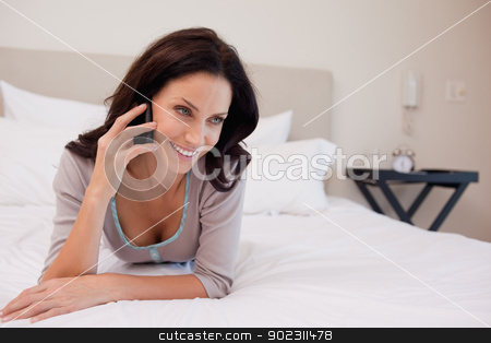 Woman laying on the bed having a phone call stock photo, Young woman laying on the bed having a phone call by Wavebreak Media
