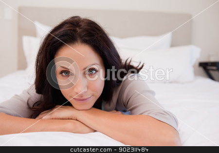 Woman relaxing on the bed stock photo, Young woman relaxing on the bed by Wavebreak Media