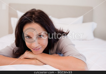 Smiling woman relaxing on the bed stock photo, Smiling young woman relaxing on the bed by Wavebreak Media