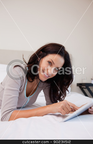Smiling woman with tablet in the bedroom stock photo, Smiling young woman with tablet in the bedroom by Wavebreak Media