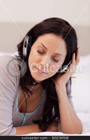 Woman laying on her bed enjoying music stock photo, Young woman laying on her bed enjoying music by Wavebreak Media