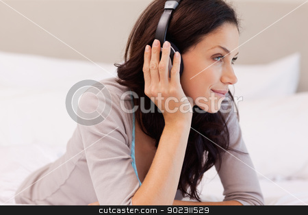 Woman with earphones on her bed stock photo, Young woman with earphones on her bed by Wavebreak Media