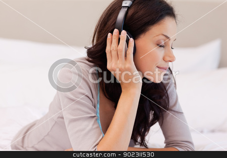 Woman enjoying music while laying on the bed stock photo, Young woman enjoying music while laying on the bed by Wavebreak Media