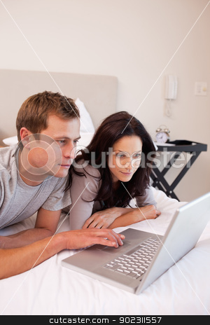Couple using laptop in the bedroom together stock photo, Young couple using laptop in the bedroom together by Wavebreak Media