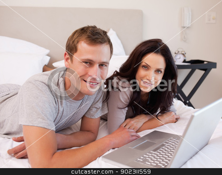 Happy couple using laptop on the bed together stock photo, Happy young couple using laptop on the bed together by Wavebreak Media