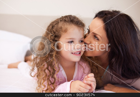 Mother whispering into her daughters ear stock photo, Young mother whispering into her daughters ear by Wavebreak Media