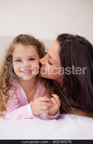 Mother kissing her daughters cheek stock photo, Young mother kissing her daughters cheek by Wavebreak Media
