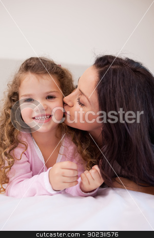 Mother giving her little daughter a kiss stock photo, Young mother giving her little daughter a kiss by Wavebreak Media