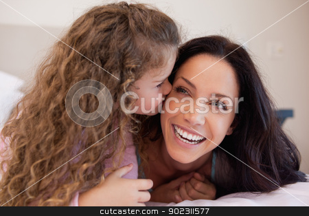 Daughter giving her mother a kiss on the cheek stock photo, Little daughter giving her mother a kiss on the cheek by Wavebreak Media