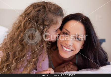 Little daughter giving her mother a kiss stock photo, Little daughter giving her young mother a kiss by Wavebreak Media