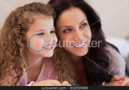 Mother and daughter lying close together stock photo, Young mother and daughter lying close together by Wavebreak Media