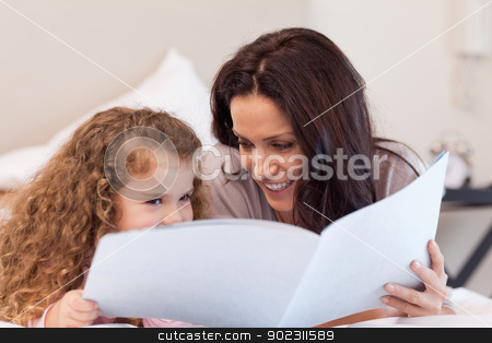 Mother and daughter reading a book together stock photo, Young mother and daughter reading a book together by Wavebreak Media