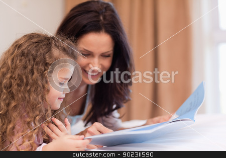 Side view of mother and daughter reading a book together stock photo, Side view of young mother and daughter reading a book together by Wavebreak Media