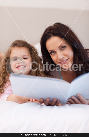 Mother and daughter reading bedtime stories together stock photo, Young mother and daughter reading bedtime stories together by Wavebreak Media