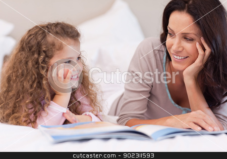 Mother reading a bedtime story for her daughter stock photo, Young mother reading a bedtime story for her daughter by Wavebreak Media