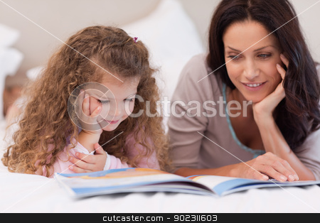 Little girl reading bedtime story with her mother stock photo, Little girl reading bedtime story with her young mother by Wavebreak Media