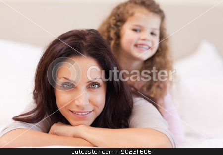 Mother and daughter relaxing on the bed stock photo, Young mother and daughter relaxing on the bed by Wavebreak Media