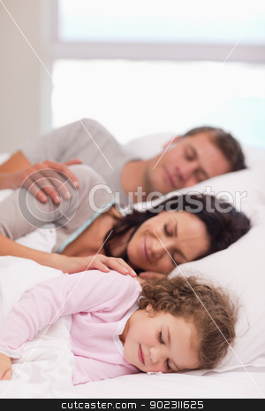 Family sleeping on the bed stock photo, Young family sleeping on the bed by Wavebreak Media