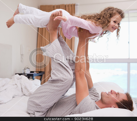 Father playing plane with his daughter stock photo, Young father playing plane with his daughter by Wavebreak Media