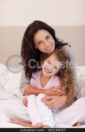 Mother hugging her daughter stock photo, Young mother hugging her daughter by Wavebreak Media