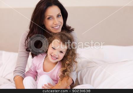 Mother hugging her daughter on the bed stock photo, Young mother hugging her daughter on the bed by Wavebreak Media