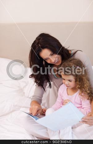 Mother reading bedtime story for her daughter stock photo, Young mother reading bedtime story for her daughter by Wavebreak Media