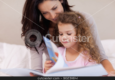 Mother reading a book with her daughter stock photo, Young mother reading a book with her daughter by Wavebreak Media