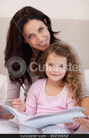 Smiling mother reading a bedtime story with her little daughter stock photo, Smiling young mother reading a bedtime story with her little daughter by Wavebreak Media