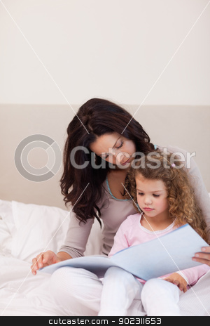 Mother reading a story for her little daughter stock photo, Young mother reading a story for her daughter by Wavebreak Media