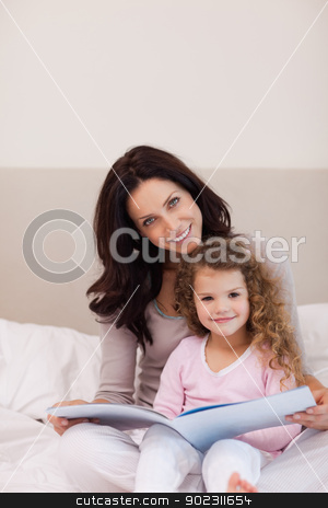 Mother and daughter reading a book on the bed stock photo, Young mother and daughter reading a book together on the bed by Wavebreak Media