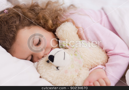 Girl hugging her teddy while sleeping stock photo, Little girl hugging her teddy while sleeping by Wavebreak Media