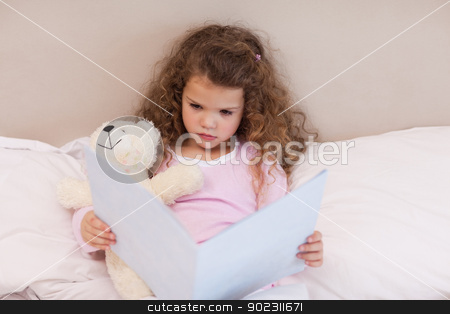 Girl looking at a book stock photo, Little girl looking at a book by Wavebreak Media