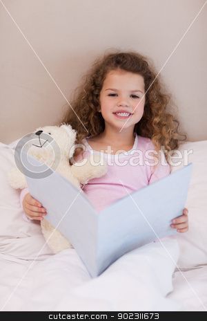 Girl sitting on the bed with a book stock photo, Little girl sitting on the bed with a book by Wavebreak Media