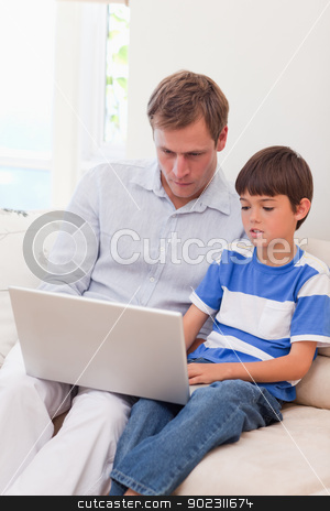 Father and son surfing the internet together stock photo, Young father and son surfing the internet together by Wavebreak Media