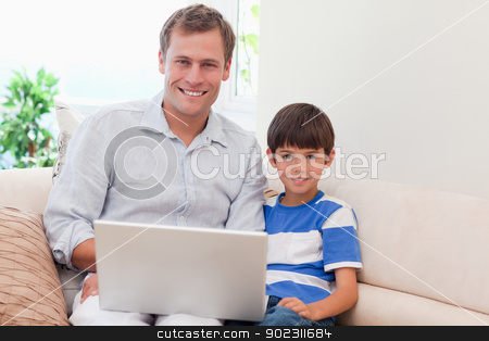 Father and son with laptop on the sofa stock photo, Young father and son with laptop on the sofa by Wavebreak Media