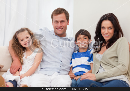 Family sitting on the sofa together stock photo, Young family sitting on the sofa together by Wavebreak Media