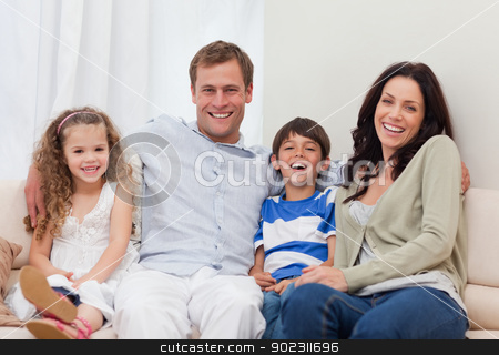 Family sitting on the couch together stock photo, Young family sitting on the couch together by Wavebreak Media