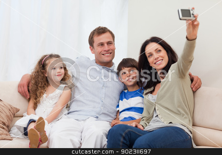 Mother taking a family picture on the sofa stock photo, Young mother taking a family picture on the sofa by Wavebreak Media