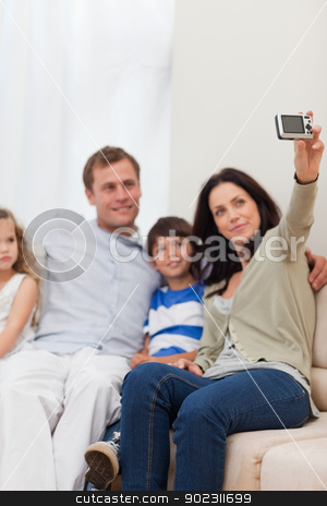 Mother taking family photograph on the sofa stock photo, Young mother taking family photograph on the sofa by Wavebreak Media