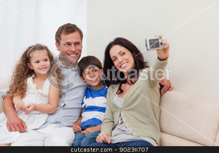 Mother taking family photograph on the couch stock photo, Young mother taking family photograph on the couch by Wavebreak Media