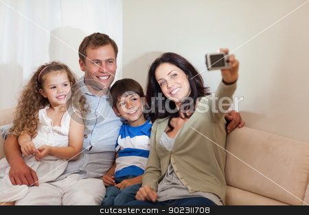 Mother taking family picture in the living room stock photo, Young mother taking family picture in the living room by Wavebreak Media
