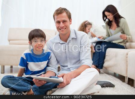 Family spending free time in the living room stock photo, Young family spending free time in the living room by Wavebreak Media