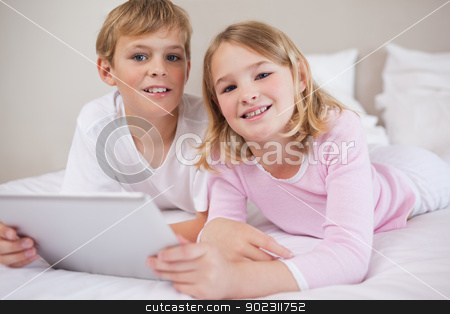 Children using a tablet computer stock photo, Children using a tablet computer in a bedroom by Wavebreak Media