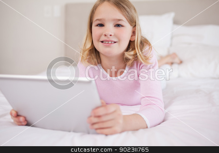 Girl using a tablet computer stock photo, Girl using a tablet computer in a bedroom by Wavebreak Media
