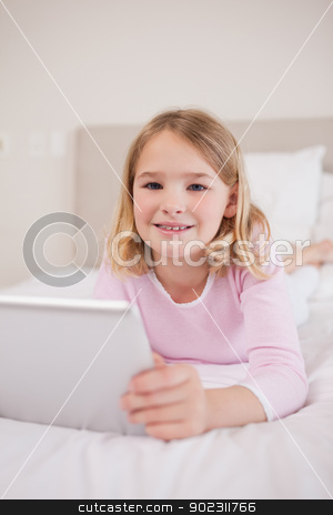 Portrait of a girl using a tablet computer stock photo, Portrait of a girl using a tablet computer in her bedroom by Wavebreak Media