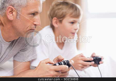 Father playing video games with his son stock photo, Father playing video games with his son in a bedroom by Wavebreak Media
